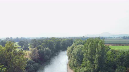 entre : A river is peacefully flowing between the trees in the middle of the countryside.