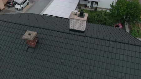 есть : We can see a blac roof on the big house. There is also a chimney. Aerial shot.