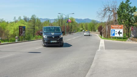 brochura : A black van with a bunch of tourists is visiting Postojna caves. Its a nice sunny day.
