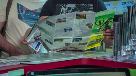 brochures : A young man who is working at the store opens a map to show something to the tourists.