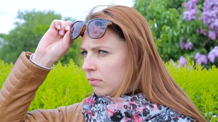 ünnepélyes : Dissatisfied girl looks at people. Woman on the park with sunglasses