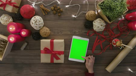 red tie : Top view hands tie a bow using digital tablet at wooden desk from above with christmass decoration