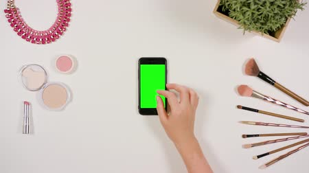 rouge : Ladys fingers zooming in on a smartphone with a green screen. The phone is on the white table. View from the top. Close-up.