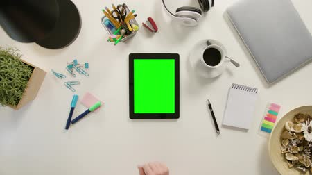 nietmachine : A finger touching a tablet with a green screen. The tablet is on the white table. View from the top. Close-up.
