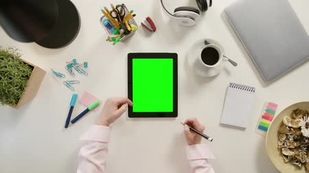 portátil : A finger scrolling on a tablet with a green screen. The tablet is on the white table. View from the top. Close-up.