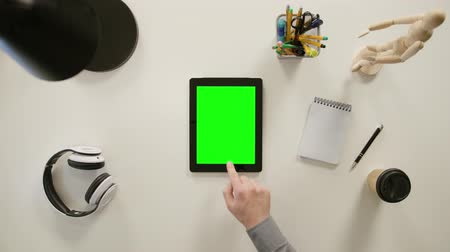 poznámkový blok : A finger touching a green screen of a tablet. The tablet is on the white table. View from the top. Close-up.