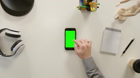 portátil : Lublin, Poland - November 2017: A finger scrolling on a phone with a green screen. The phone is on the white table. View from the top. Close-up.