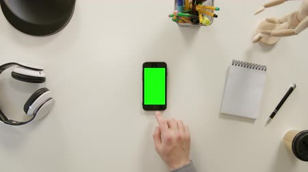 sleeve : Lublin, Poland - November 2017: A finger scrolling on a phone with a green screen. The phone is on the white table. View from the top. Close-up.