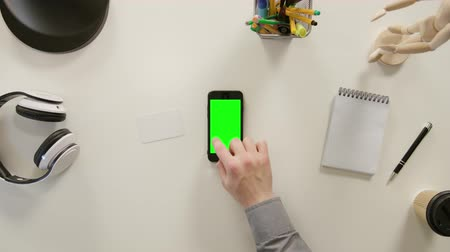 portátil : Lublin, Poland - November 2017: A finger touching a green screen of the phone. The phone is on the white table. View from the top. Close-up.