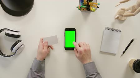 sleeve : Lublin, Poland - November 2017: A finger touching a green screen of the phone and holding a business card. The phone is on the white table. View from the top. Close-up.