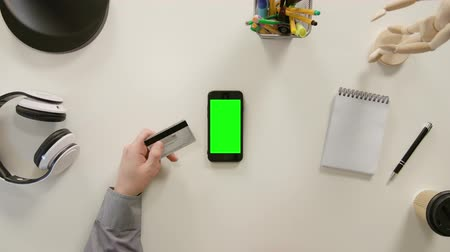 pedleri : Lublin, Poland - November 2017: A finger touching a green screen of the phone and holding a credit card. The phone is on the white table. View from the top. Close-up. Stok Video