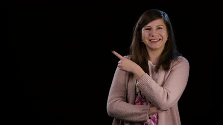 hajtogatott : An attractive smiling young lady with folded arms pointing her finger and wearing a pink sweater against a black background. Medium shot Stock mozgókép