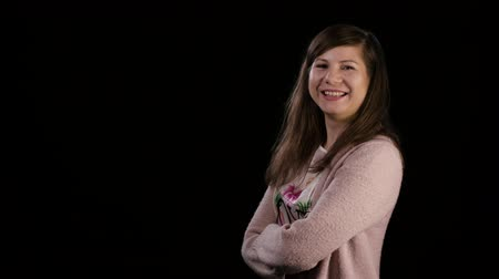 hajtogatott : An attractive smiling young lady with folded arms wearing a pink sweater against a black background. Medium shot Stock mozgókép