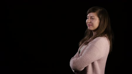 sırıtma : An attractive smiling young lady with folded arms wearing a pink sweater against a black background. Medium shot Stok Video