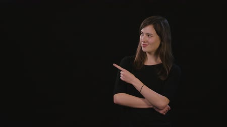 acteren : A beautiful young lady smiling and standing with her arms folded and pointing with her finger against a black background. Medium Shot Stockvideo