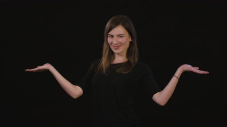 dark eyes : A beautiful young lady spreading her arms against a black background. Medium Shot Stock Footage
