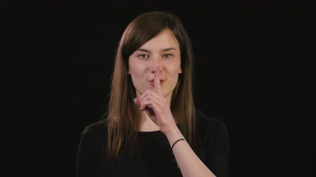 acteren : A beautiful young lady showing a shhh meme against a black background. Medium Shot Stockvideo