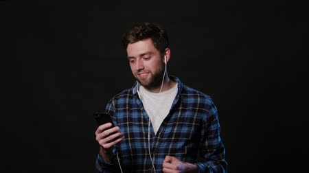 mms : An attractive young man listens to music using a phone against a black background. Medium Shot