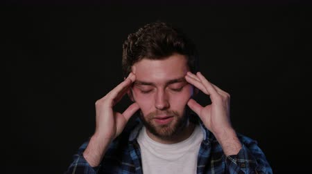 dor de cabeça : A young man immitating a headache against a black background. Close-up Shot