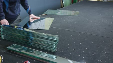 mirror glass : Cutting glass process. Men in gloves cutting glass. Close-up shot Stock Footage
