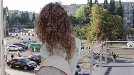 kıvırcık : Girl with curly hair waiting for a friend in the city. View from the back, slow motion. Stok Video