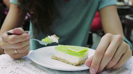 desszertek : Girl eating cheesecake with lime in a summer cafe, slow motion