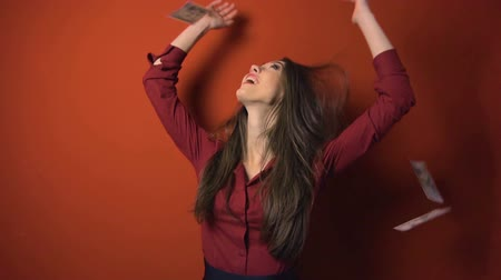 sampiyonlar : Attractive brunette woman with falling dollars banknotes red background, jackpot concept Stok Video