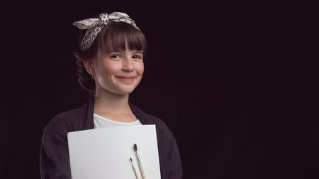 leisureactivity : Portrait of young artist painter girl smiling to camera before black background, holding brushes and album Stock Footage