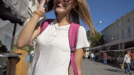 Attractive smiling caucasian tourist girl in stylish sunglasses is talking on the phone and turning around happily in the old city center, sunny day, slow motion