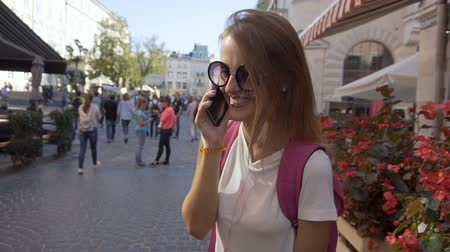 Beautiful smiling caucasian tourist girl in stylish sunglasses is talking on the phone happily in the old city center, sunny day, slow motion 影像素材