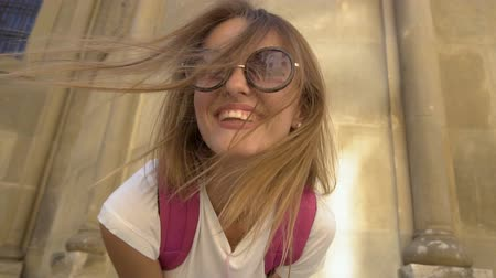 Beautiful caucasian fair hair girl in stylish sunglasses and with a pink backpack is having fun in front of an old building in the background, sunny day, slow motion