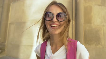 Beautiful caucasian fair hair girl in stylish sunglasses and with a pink backpack is smiling in front of an old building in the background, sunny day, slow motion Vídeos