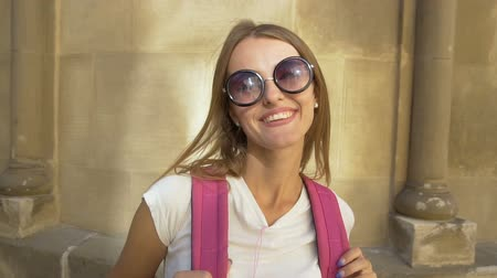 Attractive caucasian fair hair girl in stylish sunglasses and with a pink backpack is posing joufully in front of an old building in the background, sunny day, slow motion Vídeos