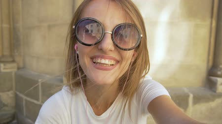 Attractive caucasian fair hair girl in stylish sunglasses is having a video chat in front of an old building in the background, sunny day, slow motion