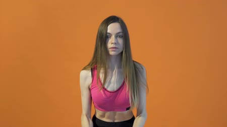Young dark hair girl, wearing a pink top, is training her back and chest with pink dumbbells in the orange background, isolated, slow motion