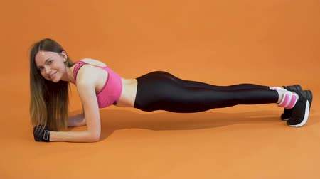 Attractive dark hair fitness instructor is doing a strong and nice plank with pleasure in the orange background, isolated, slow motion