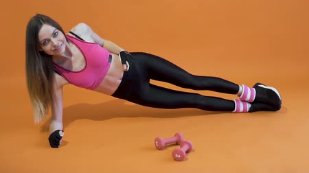 Young and attractive dark hair girl, wearing a pink top and black leggins, is doing abs workout joyfully in the orange background, isolated, slow motion Vídeos