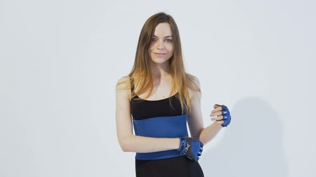 Dark hair girl, wearing a black top and leggins, is putting on a blue belt around her back in the white background, isolated, slow motion Vídeos