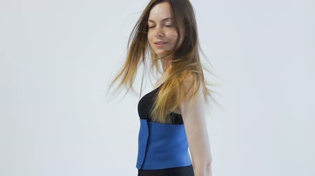 Dark hair girl, wearing a black top, a blue belt and black leggins, is turning around joyfully in the white background, isolated, slow motion Vídeos