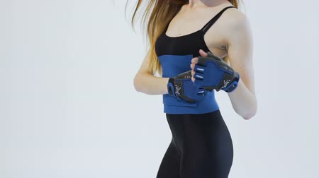 Easy-going dark hair girl, wearing a black top and leggins, is showing how to put a blue belt around her back in the white background, isolated, slow motion