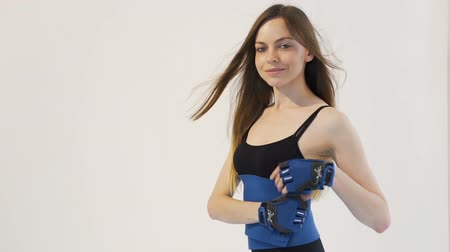 Dark hair girl, wearing a black top and leggins, is demonstrating how to put a blue belt around her back in the white background, isolated, slow motion Vídeos