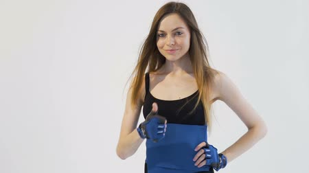 Dark hair girl, wearing a black top and black leggins, is expressing her satisfaction of blue back belt in the white background, isolated, slow motion Vídeos