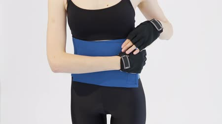Slim girl, wearing a black top and black leggins, is demonstrating how to put on a blue back belt in the white background, isolated, slow motion 影像素材