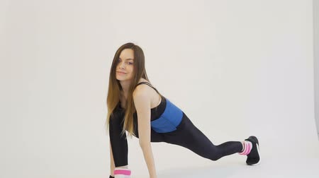 Dark hair girl, wearing a black top and leggins, is doing stretching in a blue belt around her back in the white background, isolated, slow motion
