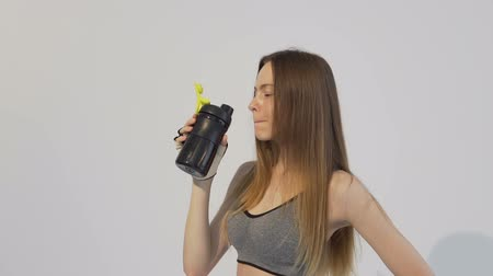 Good-looking dark hair girl, wearing a grey top, is drinking some water after tough workout in the white background, isolated, slow motion