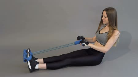 Dark hair girl, in a grey top and black leggins, is training her bicebs with a curl rope in the grey background, isolated, slow motion Vídeos