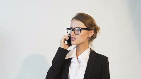 Good-looking young dark hair caucasian businesswoman, in a white blouse and a black jacket, is doing business on the phone in the white background, isolated, slow motion
