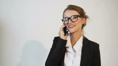 Attractive young dark hair caucasian businesswoman, in a white blouse and a black jacket, is doing business on the phone with pleasure in the white background, isolated, slow motion Vídeos