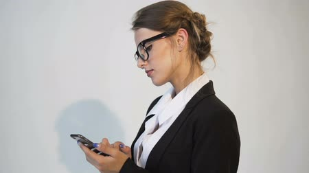 Attractive young dark hair caucasian businesswoman, in a white blouse and a black jacket, is texting a message on the phone in the white background, isolated, slow motion