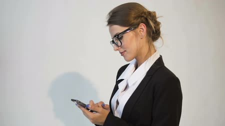Good-looking young dark hair caucasian businesswoman, in a white blouse and a black jacket, is texting a message on the phone in the white background, isolated, slow motion